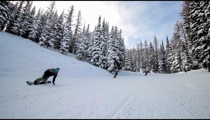 Two snowboarders and a skier making turns on open ski run