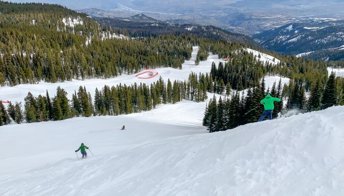 View of skiers from a far with valley and river below