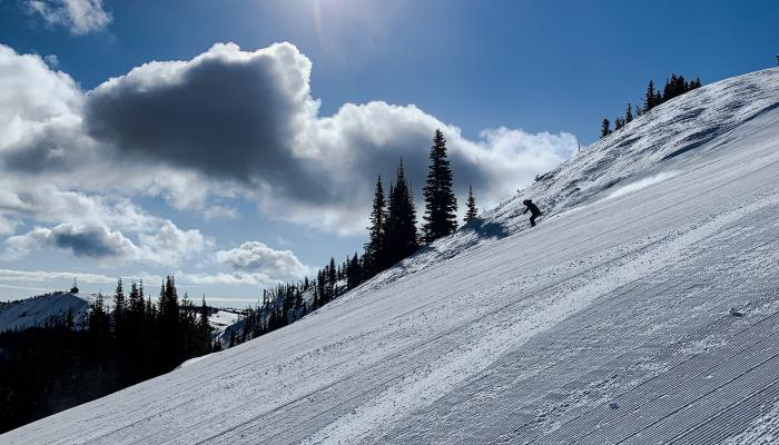 Image of skier in the distance with sun and clouds behind