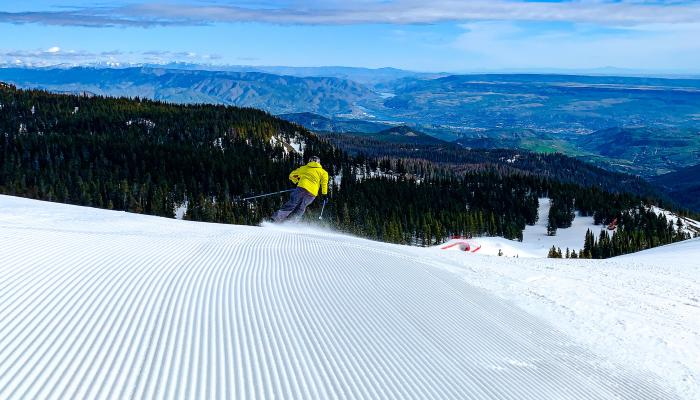 skier in yellow coat descending groomed slope with the columbia river in the background