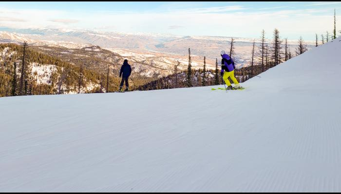 two skiers at the top of Skookum with the valley and columbia river in the background