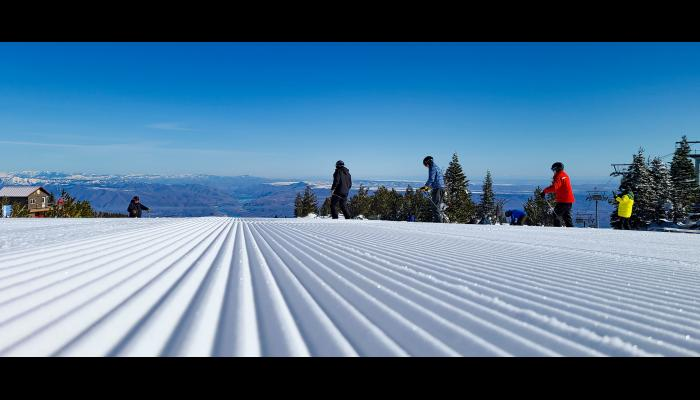 Close up of Fresh Corduroy and skiers heading down Sunspot with Columbia River in the background