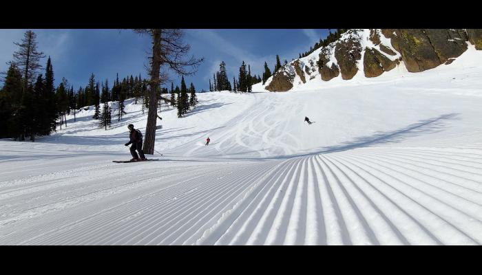 fresh corduroy with skiers and bomber cliffs in background