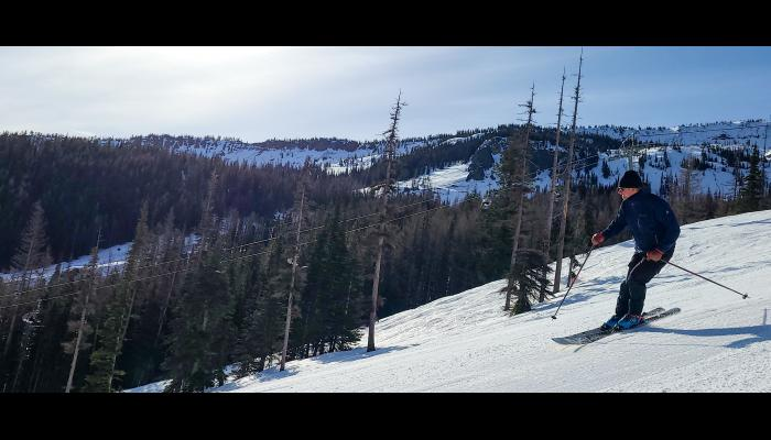 Skier making a turn with microwave tower in background