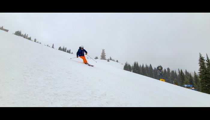 Skier making a turn on Sunspot with the Yeti in the background and snowing