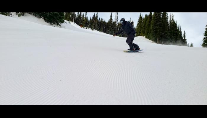 Snowboarder making a turn on a groomed run