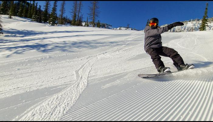 snowboarder on a groomed run making a turn with the bomber cliffs in the background