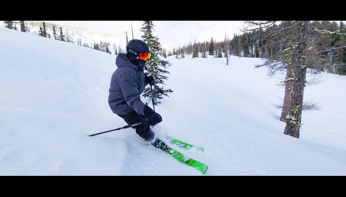 Skier making a turn through some trees with Bomber Cliffs in the background