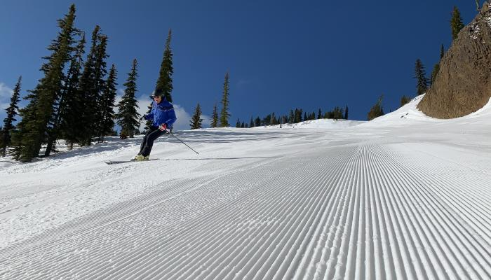 Close up of groomed snow with skier
