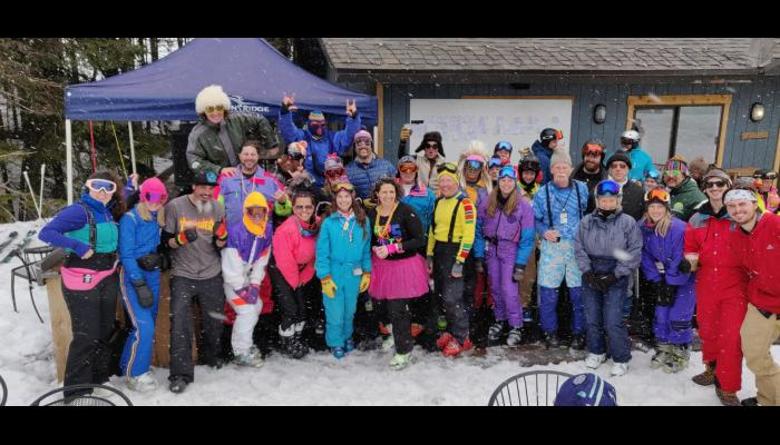 Skiers in retro costumes posing for a group picture