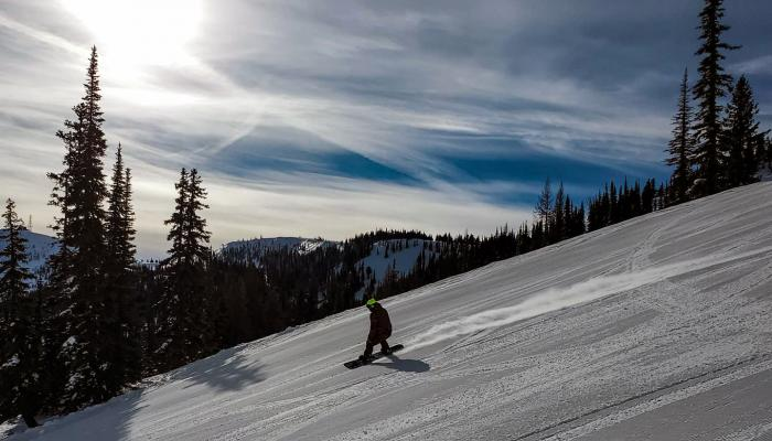 Snowboarder on groomed run with sun behind
