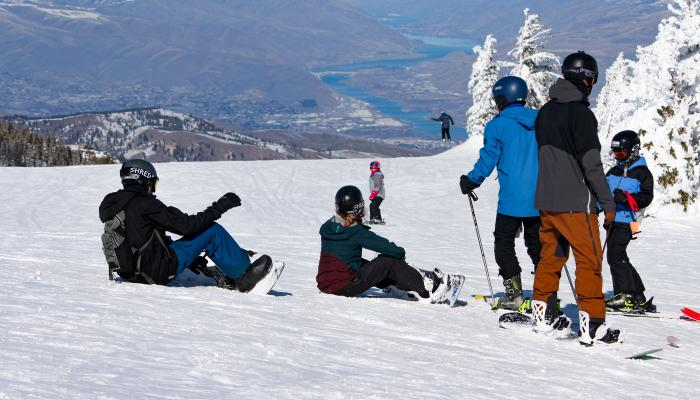 Group of skiers and snowboarders sitting at the top of the Wenatchee Express looking down at the Columbia River