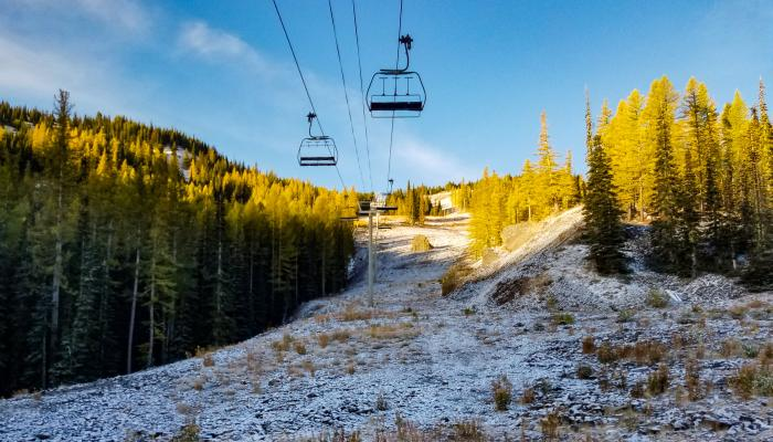 Light snow covering grass under chairlift