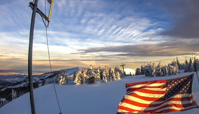 American flag waving in the breeze with sunset behind