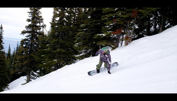 Snowboarder making turn and dragging hand on the snow