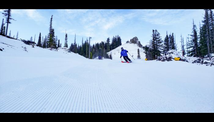 Skier on fresh Groomer with Castle Rock in the background
