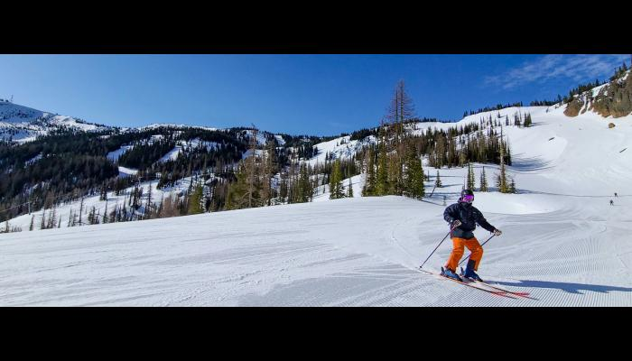 Skier on Groomed run with Bomber Bowl and microwave in the Background