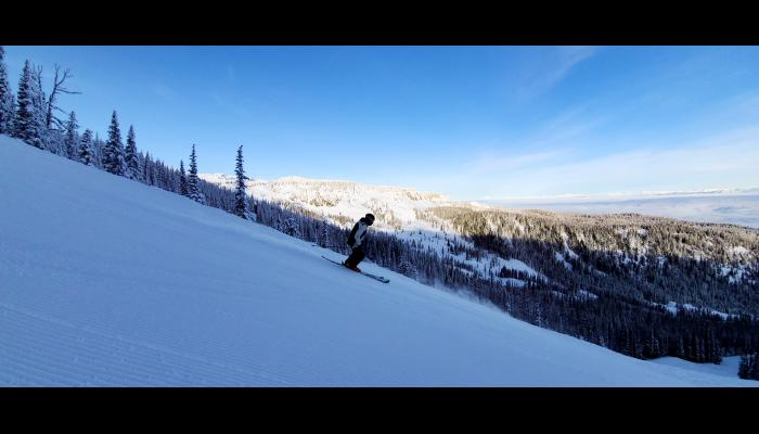 Skier making a turn with bomber cliffs in background