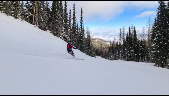 Skier making a turn with a powder spray and the valley in the background on a cloudy day