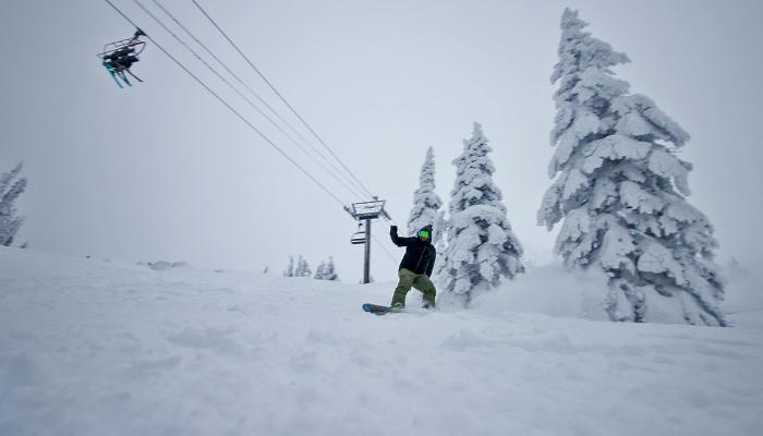 Snowboarder Making Powder Turn With Chairlift Behind
