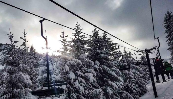 Chairlift with snow covered trees behind