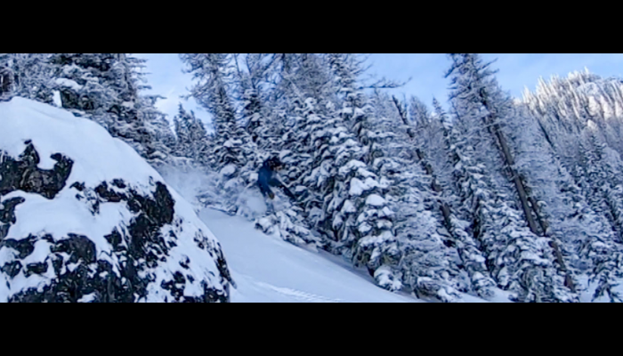 Snowboarder jumping by a rock