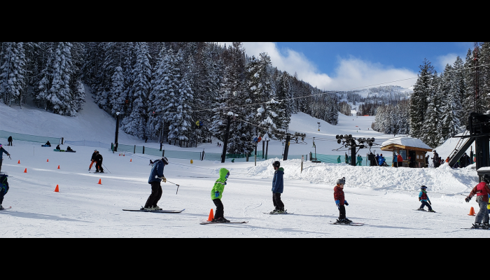 Kids taking a lesson with a chair lift in the back ground and another run with more skiers.