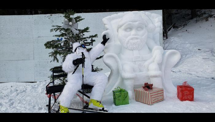 A person in a Yeti costume highfiving a snow santa