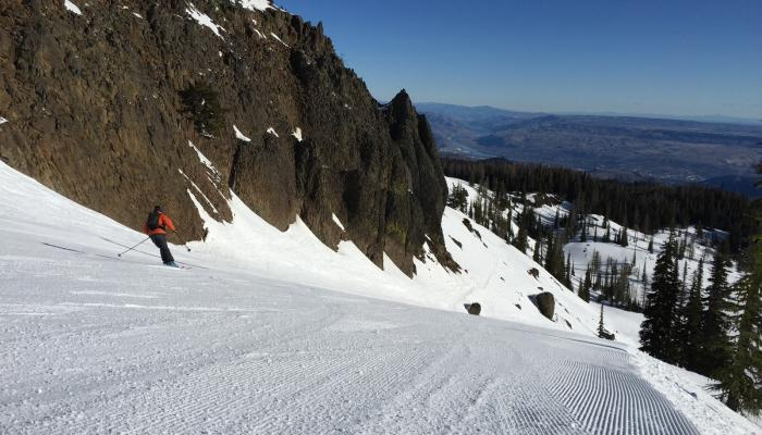 Skier on groomed run with a big view of Wenatchee below