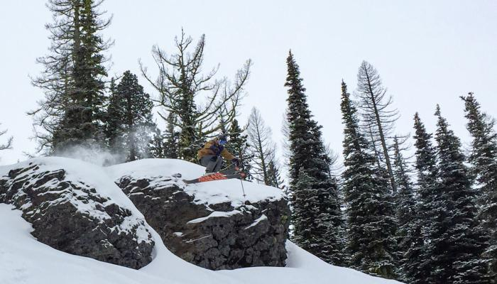 skier jumping of a rad cliff