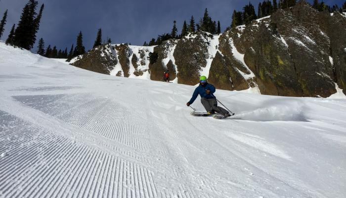 skier laying trench on a sunny groomer