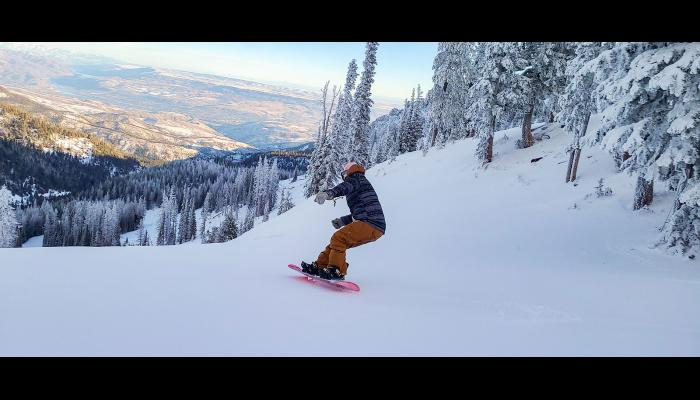 Snowboarder turning with clear valley views and the Columbia River in the background